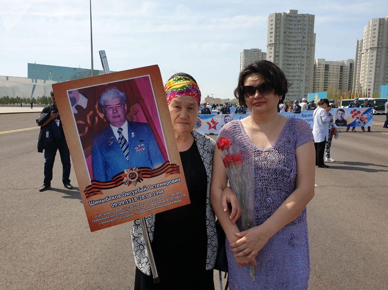 Раиса Шиныбекова держит в руке транспарант с портретом отца
