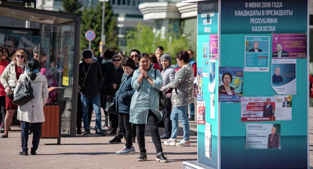 Уличная тумба с плакатами с изображением кандидатов в президенты РК