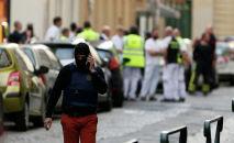 Офицер полиции говорит по мобильному телефону возле места взрыва в центре Лиона, Франция, 24 мая 2019 года