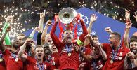 Джордан Хендерсон из «Ливерпуля» празднует с трофеем и товарищами по команде после победы в финале Лиги чемпионов