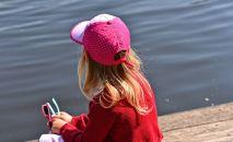 Девочка сидит на берегу