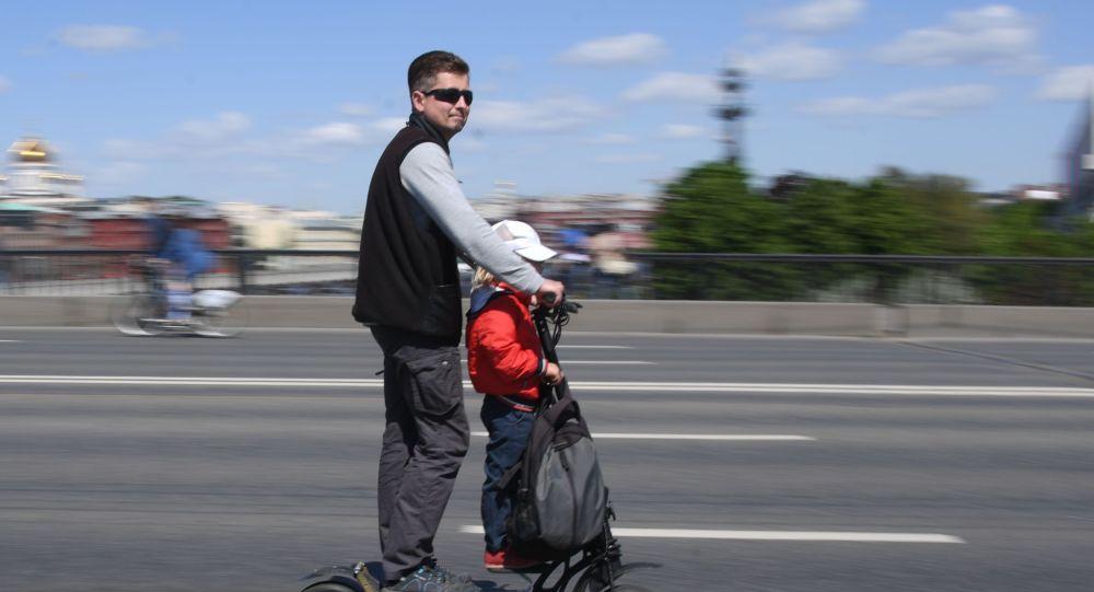 Мужчина с ребенок едут на электросамокате