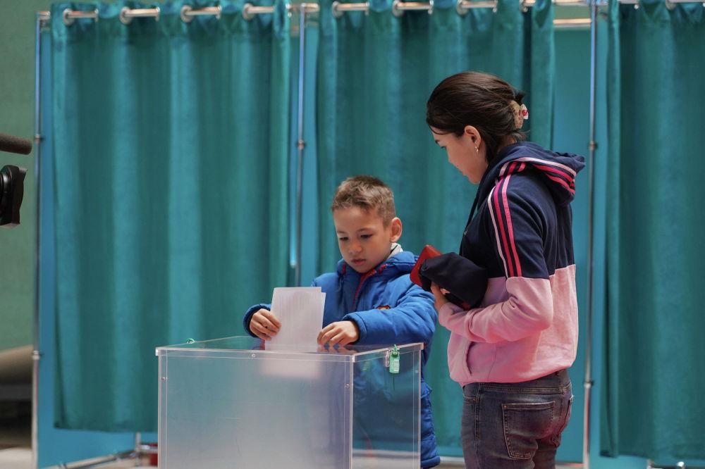 Мальчик кладет избирательный бюллетень вместо совершеннолетней сестры в Нур-Султане