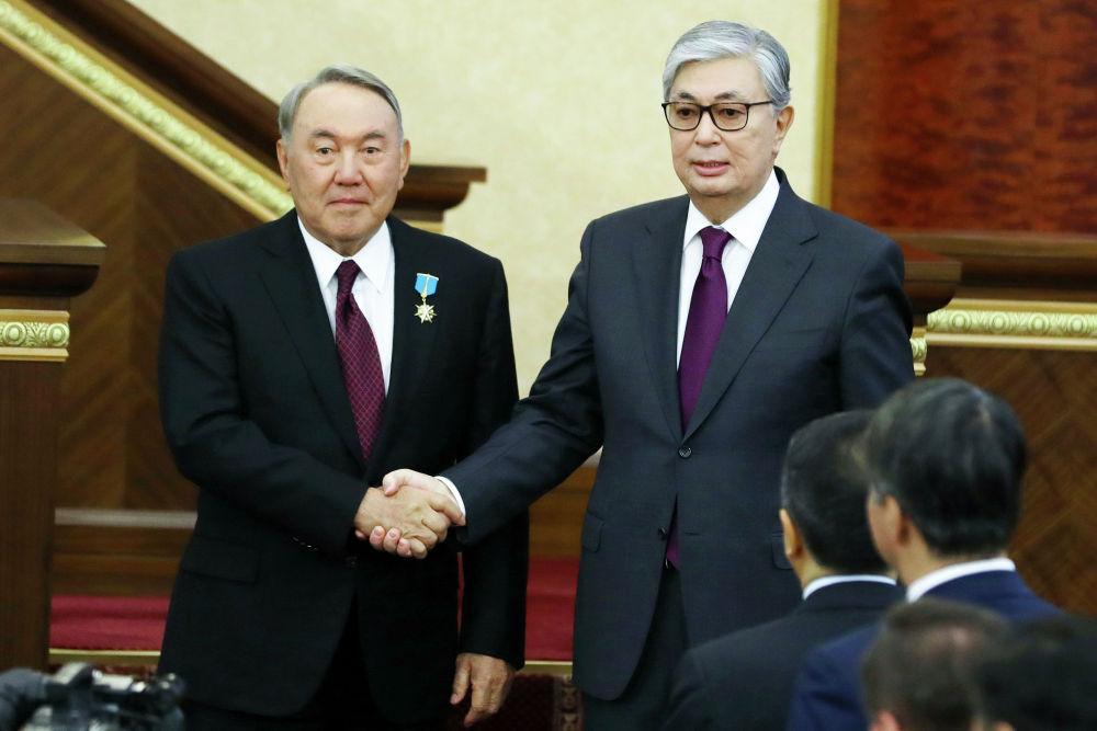 Временный президент Казахстана Касым-Жомарт Токаев  и первый президент Казахстана Нурсултан Назарбаев пожимают друг другу руки после церемонии инаугурации в Астане, Казахстан, 20 марта 2019 года