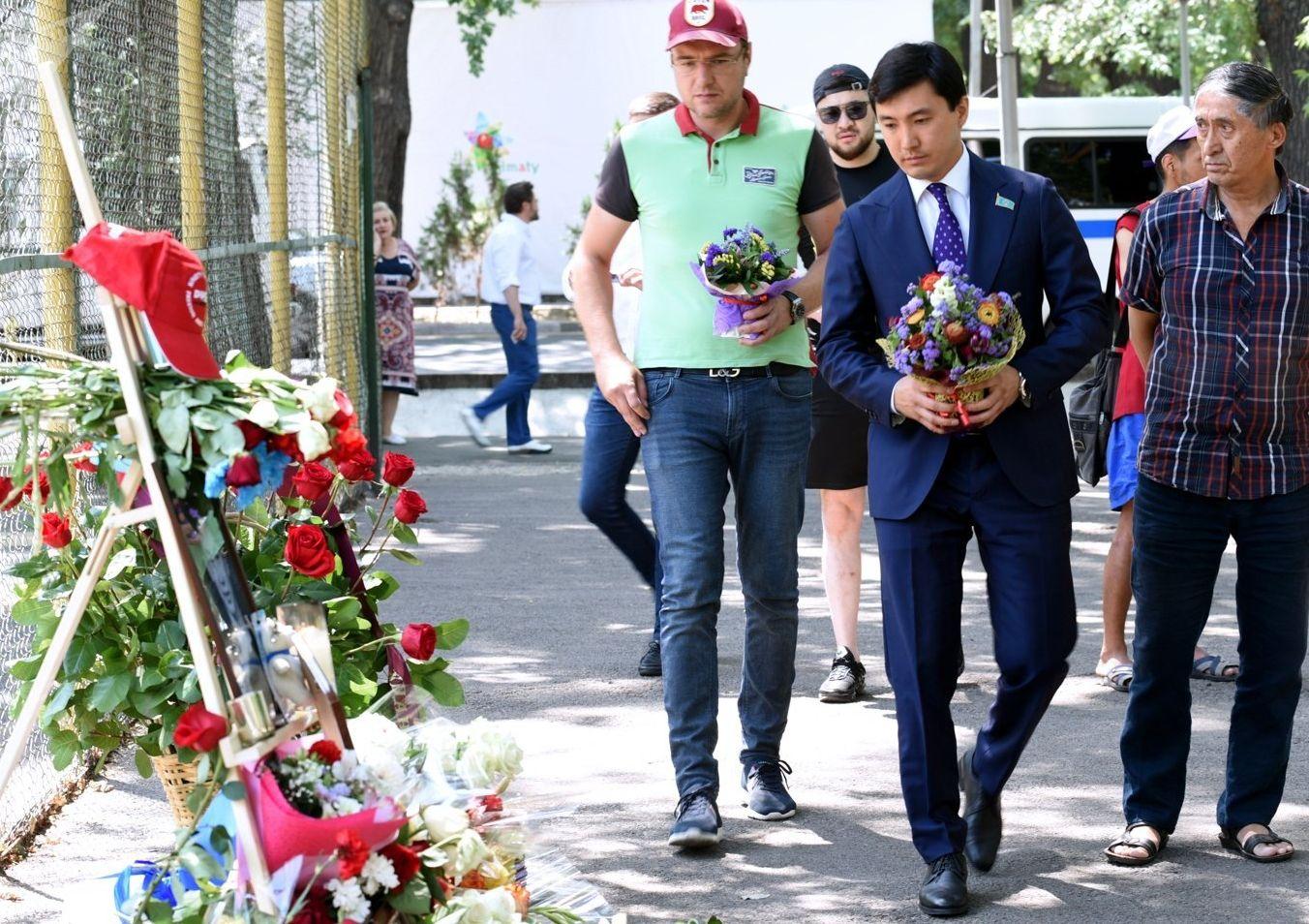 Казахстанцы несут цветы к месту трагедии, где был убит фигурист Денис Тен, в Алма-Ате