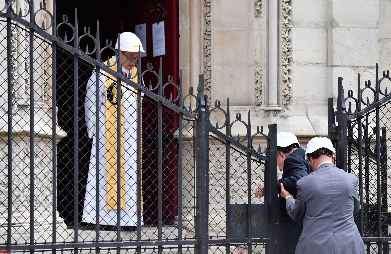 Настоятель cобора Парижской Богоматери Патрик Шове (слева) встречает у входа в собор людей, прибывших на мессу