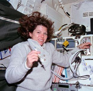 Астронавт Мэри Эллен Вебер работает со шприцем, связанным с системой разработки биореактора