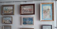 Картины на выставке, посвященные 267-летию Петропавловска, на которых художник изобразил не только памятники архитектуры, но и городские пейзажи – зарисовки улиц с домами, пешеходами и транспортом