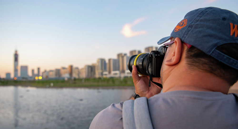 Мужчина с фотоаппаратом на береку реки Ишим