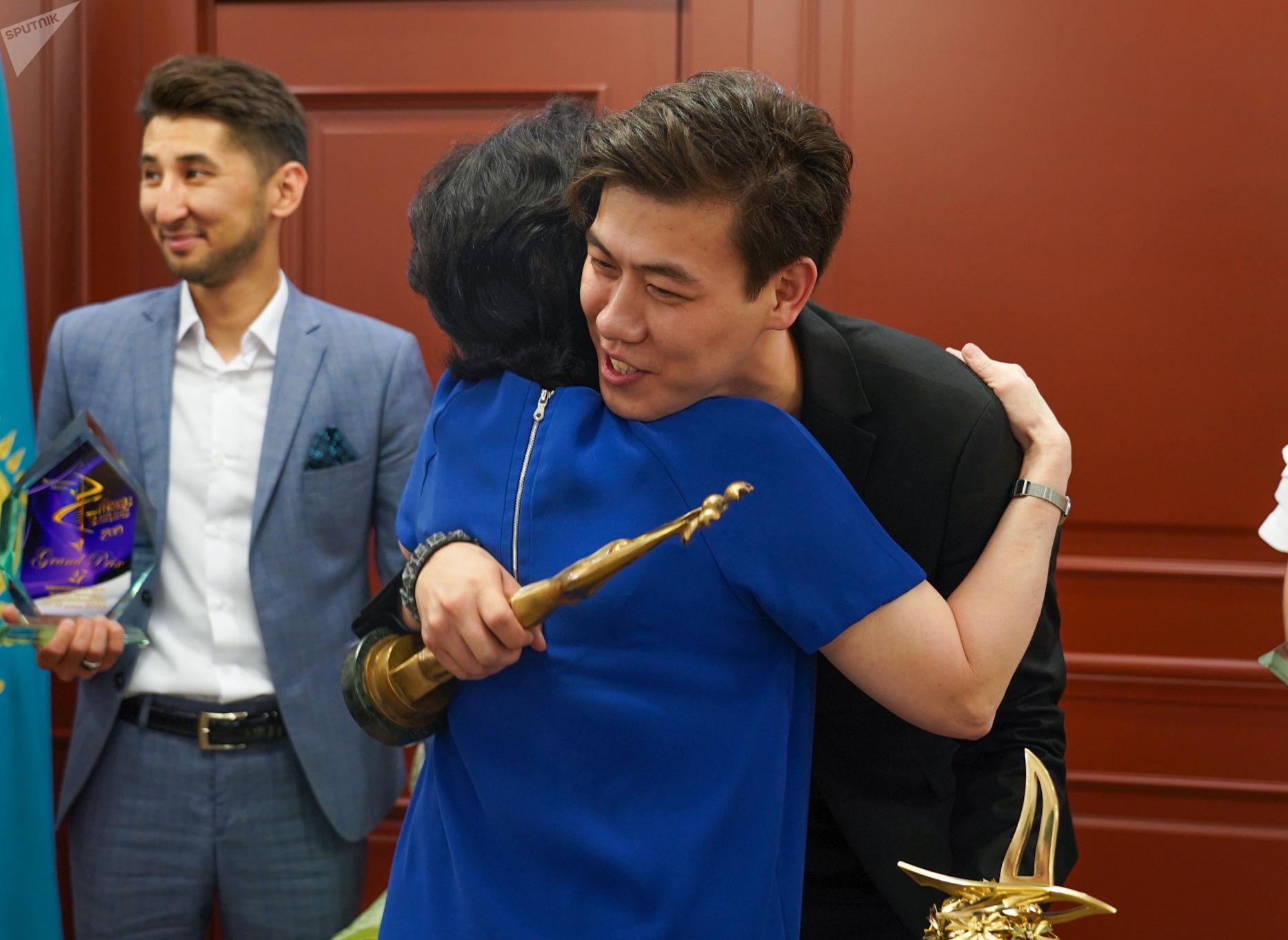 Министр культуры Актоты Раимкулова поздравляет Адильхана Макина с победой на Славянском базаре
