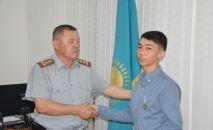 Врио главы ДЧС Алматинской области Сериккан Тураров вручил награду Алмасу Рызайбекову за спасение трех детей из пожара