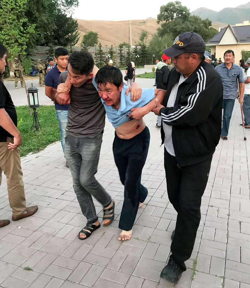 Сторонники бывшего лидера Кыргызстана выводят раненого после захвата резиденции
