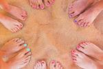 Красивые загорелые ножки с ярким маникюром на песке