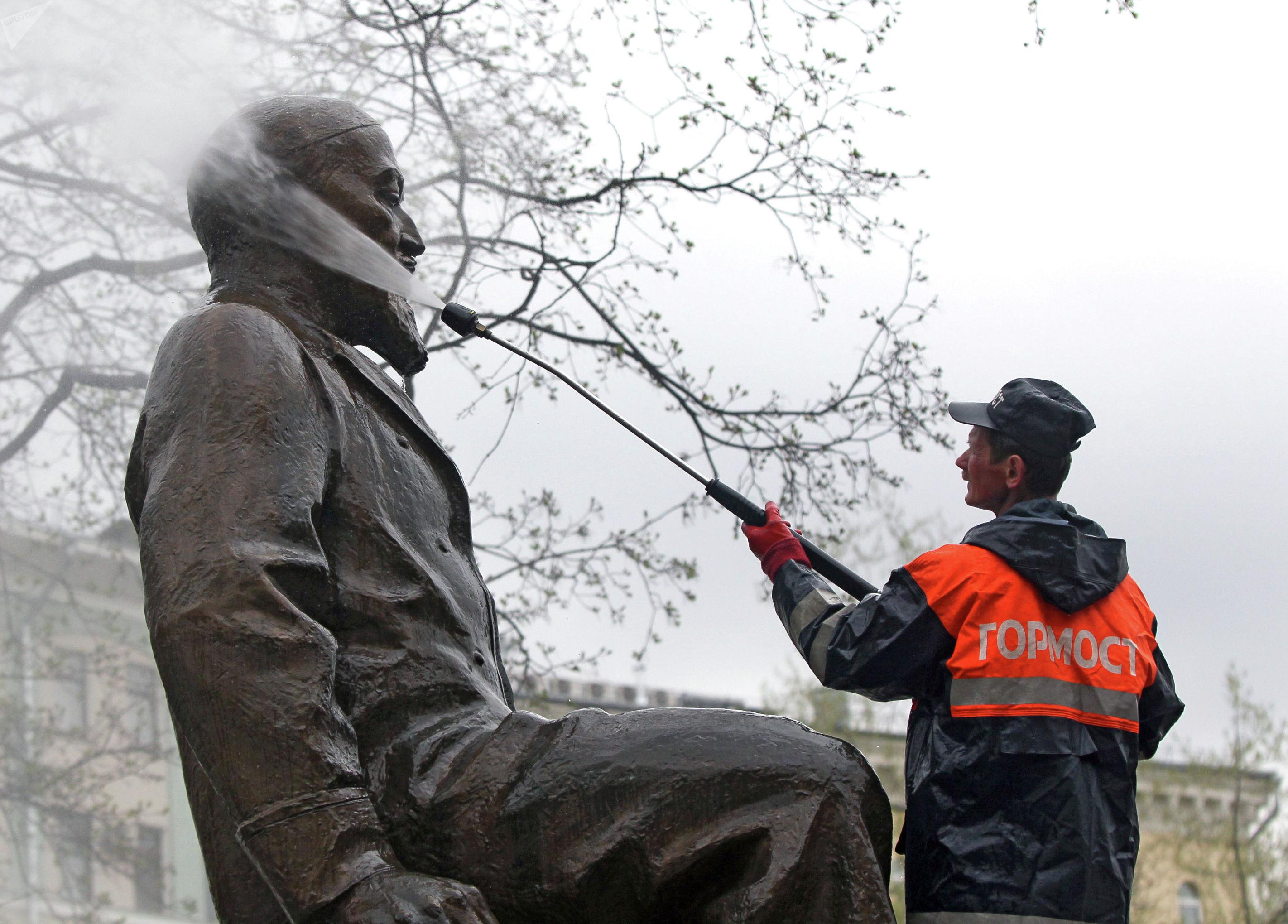 Сотрудник городской коммунальной службы моет памятник писателю Абаю Кунанбаеву на Чистопрудном бульваре в Москве