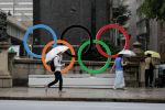 Пассажиры проходят мимо Олимпийских колец