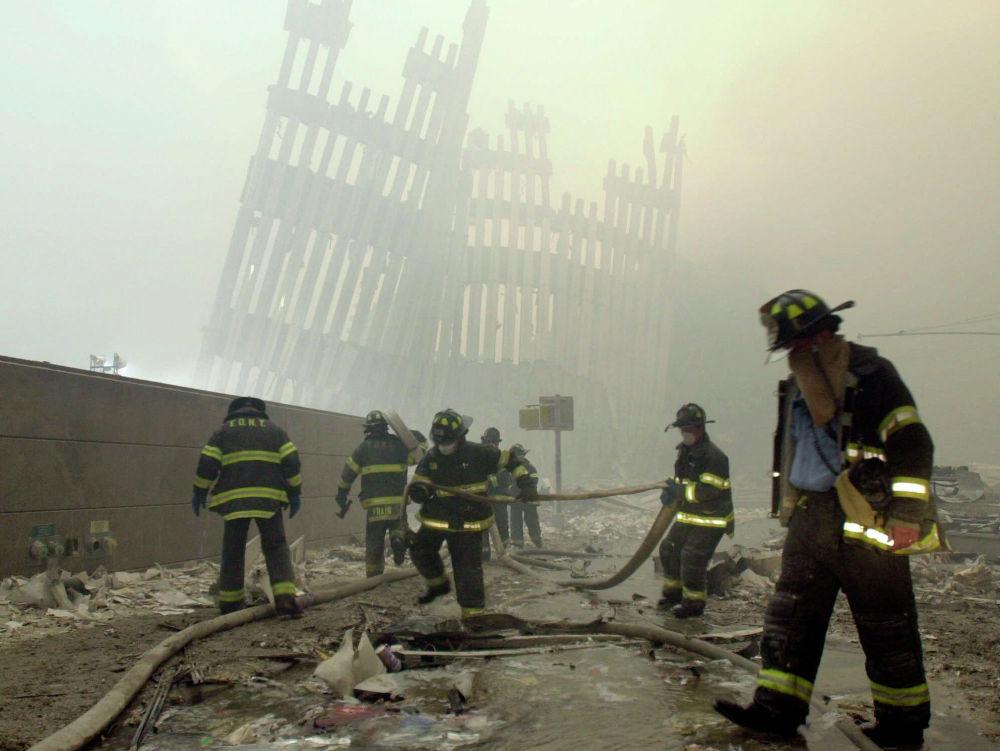 Пожарные Нью-Йорка работают среди мусора на улице Кортландт после террористических атак 11 сентября