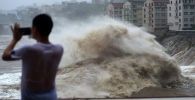Мужчина снимает приближение тайфуна, архивное фото