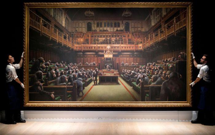 Ассистенты галереи Sotheby's представляют работу британского уличного художника Бэнкси под названием Devolved Parliament