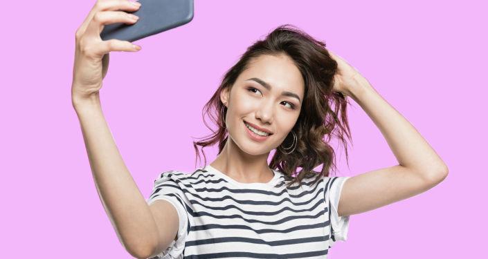 Девушка улыбается и делает селфи на свой смартфон