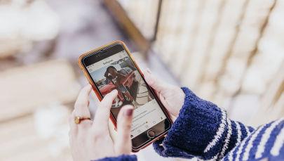 Девушка держит в руках смартфон с открытым приложением Instagram