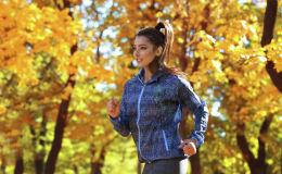 Девушка в осенней спортивной куртке занимается бегом в парке
