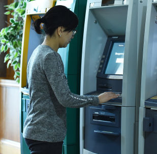 Девушка у банкомата, архивное фото