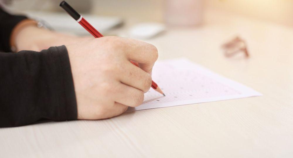 Человек пишет на листе бумаги, иллюстративное фото
