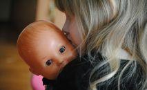 Девочка держит куклу