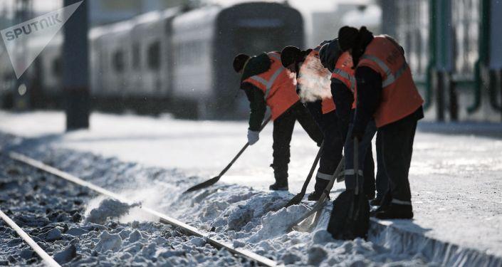 Рабочие очищают железнодорожный путь, архивное фото