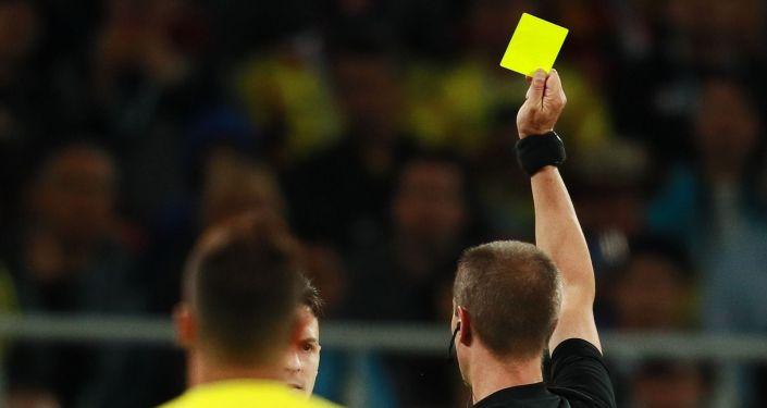 Судья показывает желтую карточку