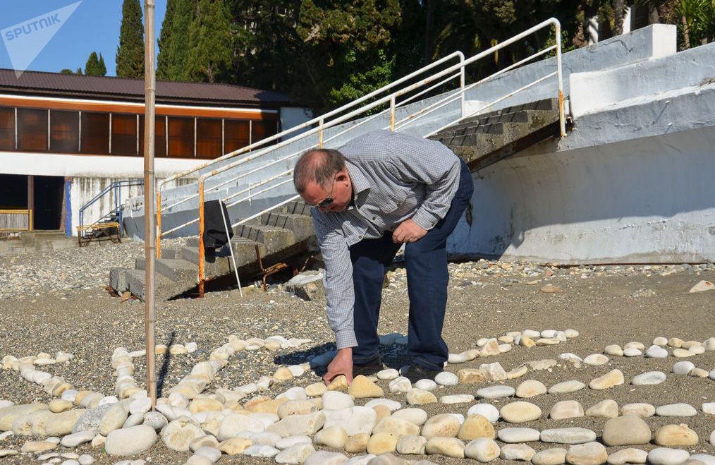 Владимир Пинчуков выкладывает солнечные часы на берегу
