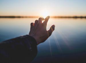 Человек протягивает руку к солнцу