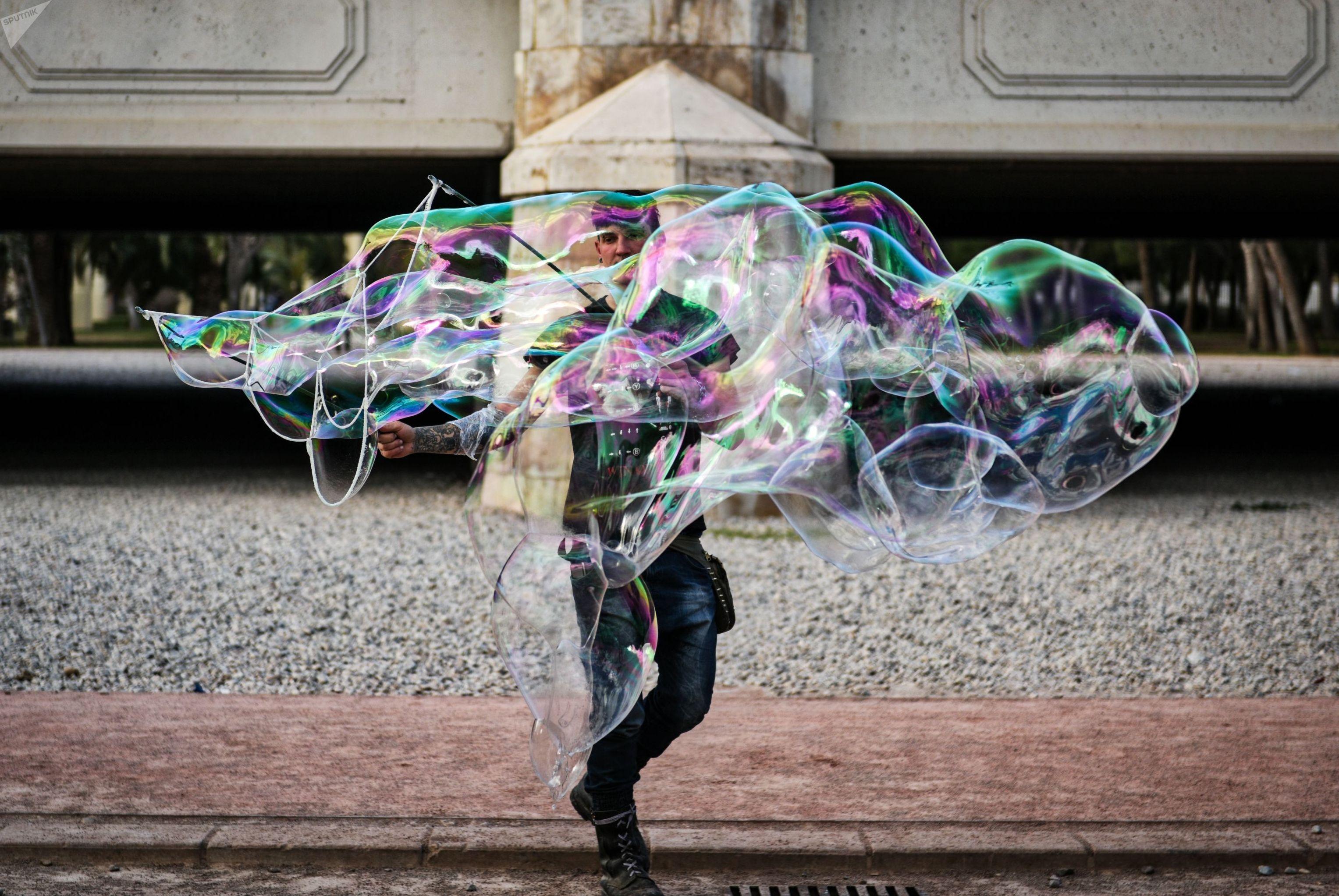 Мужчина создает огромные мыльные пузыри возле моста Анхель Кустодио в парке, находящемся на месте старого русла реки Турии в Валенсии