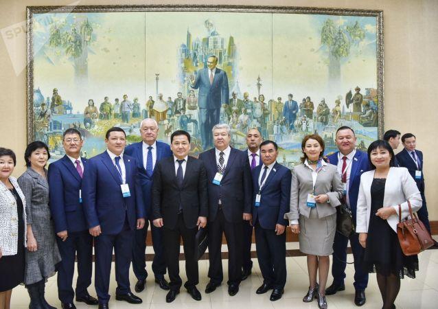 Делегаты съезда Nur Otan делают памятные снимки у картины с портретом первого президента Нурсултана Назарбаева