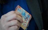 Мужчина кладет деньги в карман пиджака, иллюстративное фото