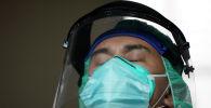 Врач в защитном костюме закрыл глаза