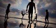 Отдыхающие на пляже играют с мячом во время пандемии коронавируса