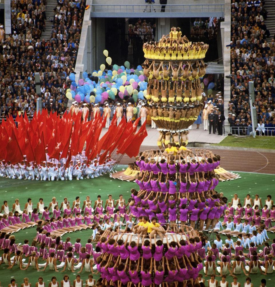 Лужники стадионындағы олимпиаданың салтанатты ашылу шарасында шеңбер мен жалаулардан фантастикалық гүлдер жасалып, керемет жанды пирамидалар көтерілді.