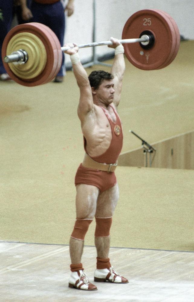 Советский штангист Виктор Мазин берёт вес на соревнованиях по тяжёлой атлетике во время проведения  XXII Олимпийских игр в Москве.