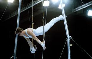 Гимнаст Александр Дитятин выступает на кольцах на Олимпиаде в Москве