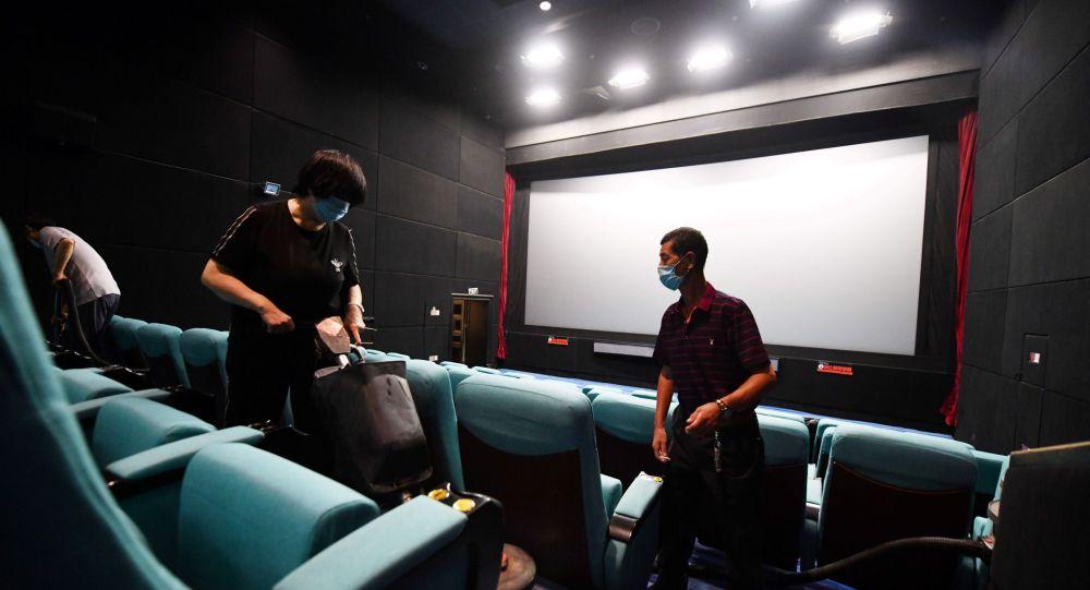 Работники кинотеатра в масках делают уборку в зрительном зале