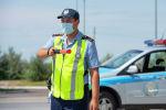 Патрульный полицейский в маске с жезлом на дороге