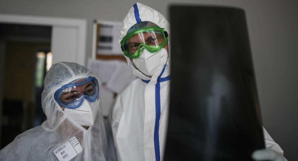 Российские врачи в защитных костюмах рассматривают рентгеновский снимок