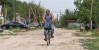 Житель поселка едет по делам на велосипеде