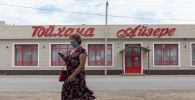 Женщина в маске проходит мимо закрытого ресторана в поселке