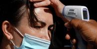 Девушке в маске измеряют температуру