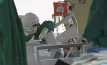 Медик в защитном костюме наблюдает за пациентом в палате интенсивной терапии в больнице с коронавирусом