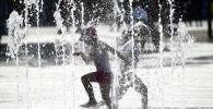Дети бегают под струями фонтана