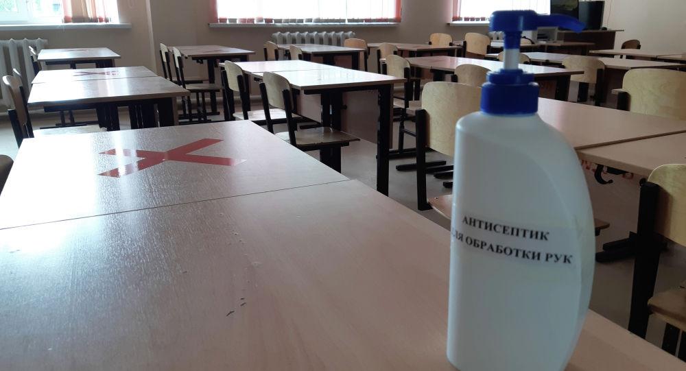 Антисептик и отметки на партах в школьном классе для соблюдения социальной дистанции