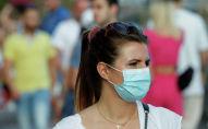 Девушка в маске гуляет на улице